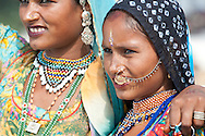 Colourful Indian women with nose piercings and beaded jewellery.
