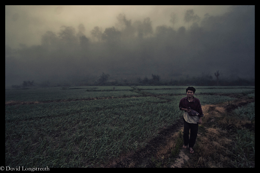 Fog enshrouds a refugee worker along the Thai-Burma border.