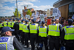 Luton, UK. 27th June, 2015. Police officers form a barrier around local residents and anti-racist activists from Unite Against Fascism at a counter-protest against a march by far-right group Britain First. A large police presence kept the two groups apart.
