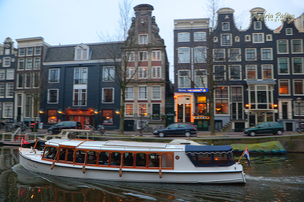 Boat sailing along the oudezijds voorburgwal canal at twilight