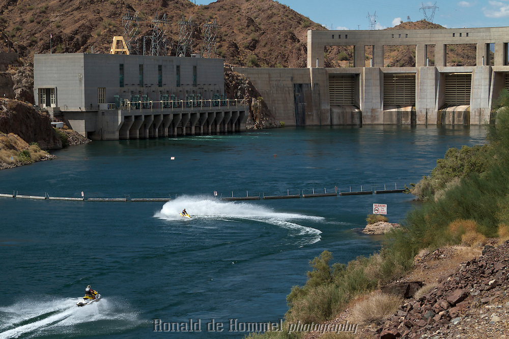 Jet skiing near the Parker Dam in the Colorado River, the 'deepest' dam in the world. Behind it is Lake Havasu. The dam was built to create a reservoir to feed the California Aqueduct end the Central Arizona Project. Two canals that supply the Los Angeles area and Phoenix and Tucson on Arizona with most of their water.