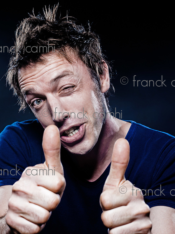 studio portrait on black background of a funny expressive caucasian man thumb up winking