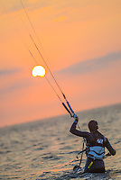 A back-view of a female kitesurfer, as seen entering into shallow waters of the North Sea on a beautiful yet windy, Summer evening, near the bay of Lauwesoog, Groningen, the Netherlands.