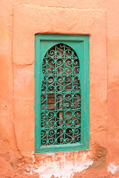 MARRAKESH, MOROCCO - 19TH APRIL 2016 - Emerald green arched window shutter with padlocks on the side of the exterior of the Zaouia / zawiya burial tomb shrine site of Sidi Abdullah al-Ghazwani, Marrakesh, Morocco.