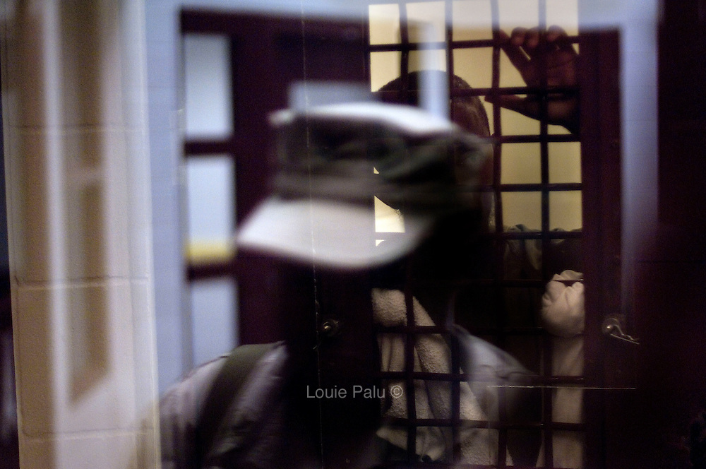 """A detainee looks out of a cell past the reflection of a US military official seen on a security window in Camp 5, which is a maximum-security detention facility where the most uncooperative as well as detainees with the most intelligence value are housed at the detention facility in Guantanamo Bay, Cuba. Approximately 250 """"unlawful enemy combatants"""" captured since the September 11, attacks on the United States continue to be held at the detention facility. (Image reviewed by military official prior to transmission)"""
