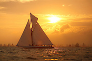 The sun rises as Kelpie, a 1903 Solent One Design gaff, crosses the start line at Cowes, Isle of Wight at the beginning of the JP Morgan Asset Management Round the Island Race.