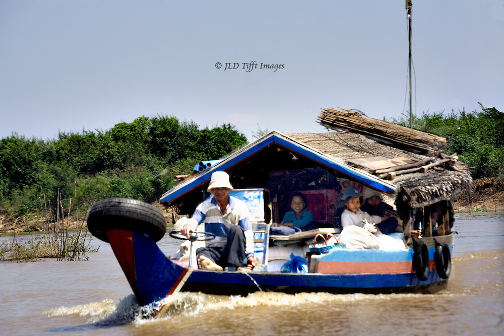 Man in a white hat steering a large motor barge packed with household goods and several family members chugs toward the camera on its way to one of the floating villages.