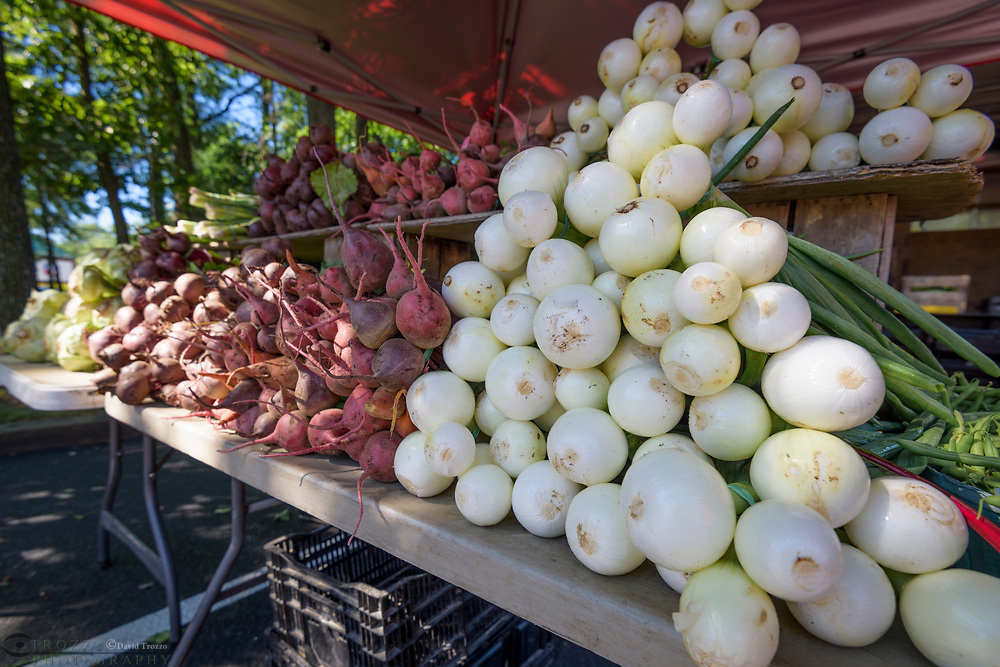 Fresh produce beats and onions for sale at a famers market.