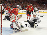 The Kings' Dustin Brown ends up on his rear end in front of Blackhawks' goaltender Corey Crawford during Chicago's 5-4 victory in Game 5 of the Western Conference Final of the 2014 NHL Stanley Cup Playoffs at United Center in Chicago Wednesday.