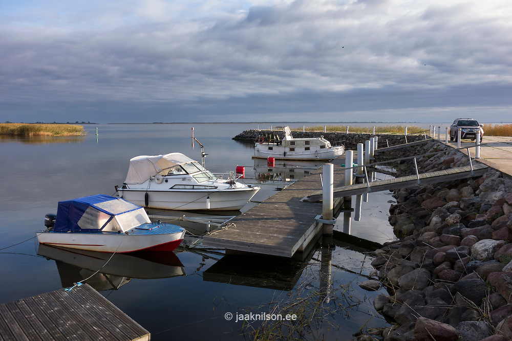 Motor boats moored to wooden pier or jetty on river or lake. Lake Peipsi. Laaksaare marina in Tartu County, Estonia.