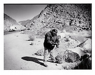 "Ricardo Ram of Angels of the Desert (Angeles del Desierto in Spanish) examines a shoe discarded beside highway, most likely my a Mexican migrant trying to enter the United States.  ""Coyotes"" (those who migrants pay to arrange passage across the US border) rendezvous with migrants who hide under bridges along this desert highway to transport them in trucks to American cities to the north...Angels of the Desert bring water to migrants and blankets in winter.  Temperatures can fall below freezing on winter nights and above 45 degrees C (110+ degrees F) in the low desert.  Footprints of scores of migrants who have passed remain in the dry river bed."