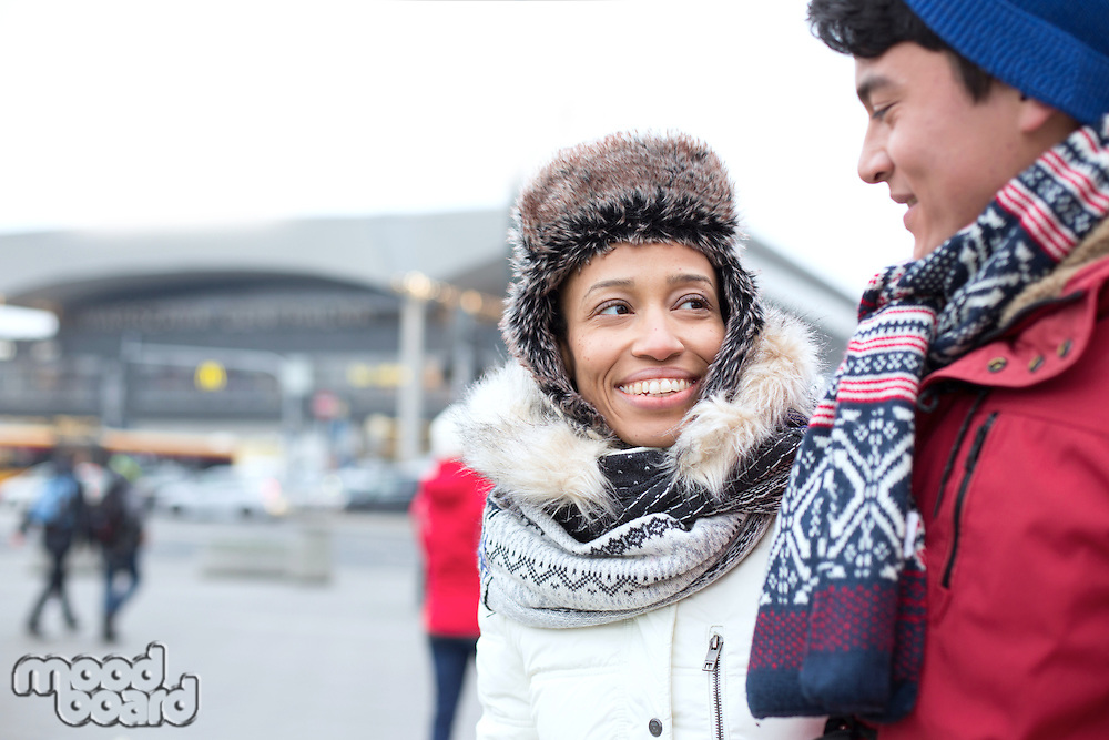 Couple talking while walking in city during winter