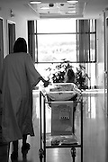 A woman in hospital gown with her newborn baby in the maternity ward after delivery