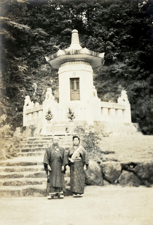 two adult Japanese people posing in front of a grave monument