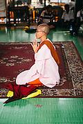 Nun worshipping inside Sule Pagoda. Yangon, Myanmar