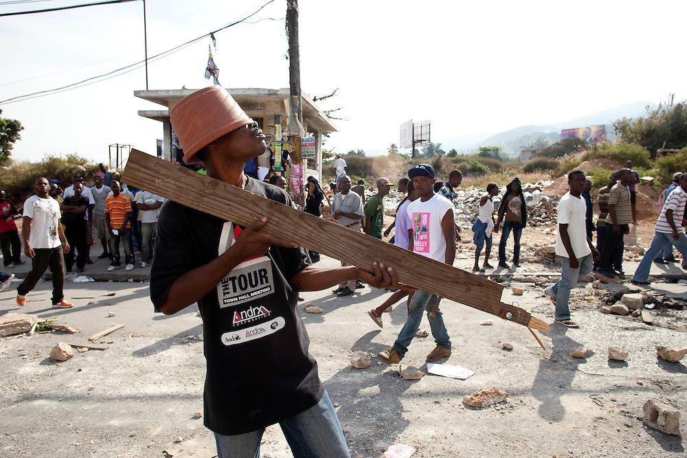"A protester holds a piece of wood in the shape of a gun. He say's ""We voted for Martelly and they gave us Manigat and Celestin"". Thousands of protestors, many of whom are supporters of Michel Martelly, take to the streets in protest after the results of the January 28th election were announced last night."