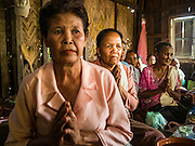 20 JUNE 2016 - DON KHONE, CHAMPASAK, LAOS: Mourners pray at a funeral in a home in Don Khone village on Don Khone Island. Don Khone Island, one of the larger islands in the 4,000 Islands chain on the Mekong River in southern Laos. The island has become a backpacker hot spot, there are lots of guest houses and small restaurants on the north end of the island.     PHOTO BY JACK KURTZ