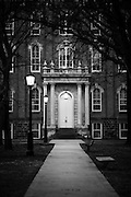 Front entrance and sidewalk to an older building on a college campus in Arkansas at dusk.