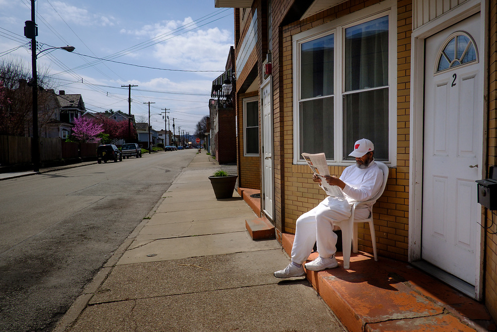 A Brackenridge, Pa., resident reads his paper outside of his home.