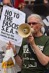 """Cricklewood, London, July 19th 2014. One of over 100 counter-protesters uses a megaphone to spread her anti-fascist message as 13 far right anti-Islamists from the """"South East Alliance"""", demonstrate outside the offices of Egypt's Muslim Brotherhood."""