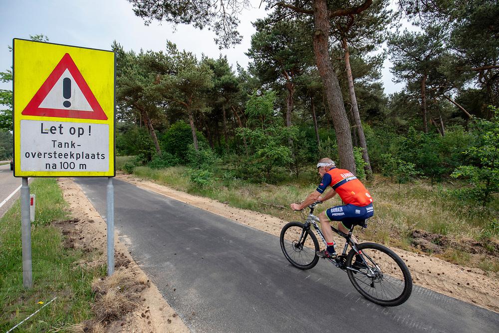 Fietsers rijden langs het natuurgebied Weerter- en Budelerbergen. Een mountainbiker passeer het waarschuwingsbord voor een tankoversteekplein. De heide wordt gebruikt als militair oefenterrein.<br /> <br /> Cyclists pass the Weerter- and Budelerbergen.