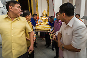 12 APRIL 2014 - BANGKOK, THAILAND: Deputy Bangkok Governor Police General ASAWIN KWANMUANG (left) and others carry the Phra Buddha Sihing out of the National Museum at the start of Songkran in Bangkok. The Phra Buddha Sihing, a revered statue of the Buddha, is carried by truck through the streets of Bangkok so people can make offerings and bathe it in scented oils. Songkran is celebrated in Thailand as the traditional New Year's from 13 to 16 April. The date of the festival was originally set by astrological calculation, but it is now fixed. The traditional Thai New Year has been a national holiday since 1940, when Thailand moved the first day of the year to January 1. The first day of the holiday period is generally the most devout and many people go to temples to make merit and offer prayers for the new year.     PHOTO BY JACK KURTZ
