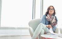 Thoughtful businesswoman sitting at table in creative office