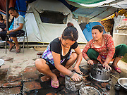 04 AUGUST 2015 - BUNGAMATI, NEPAL: Women do their dishes in front of their tents in Bungamati, a village about an hour from Kathmandu. Three months after the earthquake many families still live in tents scattered around the village. The Nepal Earthquake on April 25, 2015, (also known as the Gorkha earthquake) killed more than 9,000 people and injured more than 23,000. It had a magnitude of 7.8. The epicenter was east of the district of Lamjung, and its hypocenter was at a depth of approximately 15 km (9.3 mi). It was the worst natural disaster to strike Nepal since the 1934 Nepal–Bihar earthquake. The earthquake triggered an avalanche on Mount Everest, killing at least 19. The earthquake also set off an avalanche in the Langtang valley, where 250 people were reported missing. Hundreds of thousands of people were made homeless with entire villages flattened across many districts of the country. Centuries-old buildings were destroyed at UNESCO World Heritage sites in the Kathmandu Valley, including some at the Kathmandu Durbar Square, the Patan Durbar Squar, the Bhaktapur Durbar Square, the Changu Narayan Temple and the Swayambhunath Stupa. Geophysicists and other experts had warned for decades that Nepal was vulnerable to a deadly earthquake, particularly because of its geology, urbanization, and architecture.    PHOTO BY JACK KURTZ