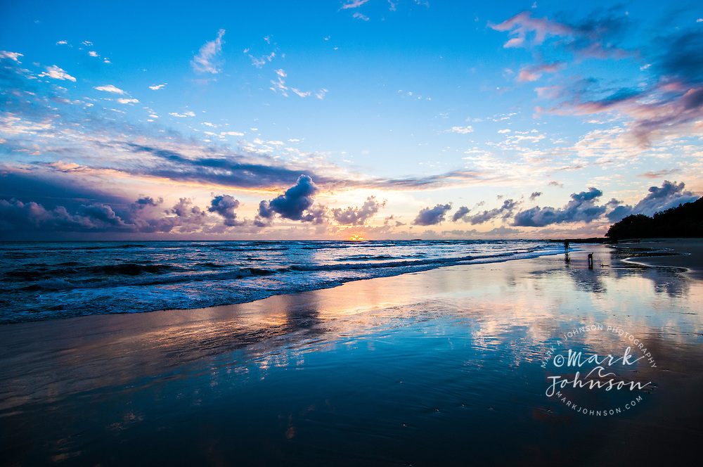 Dog & owner walking on the beach at sunrise, Deadman's Beach, N. Stradbroke Island, Queensland, Australia