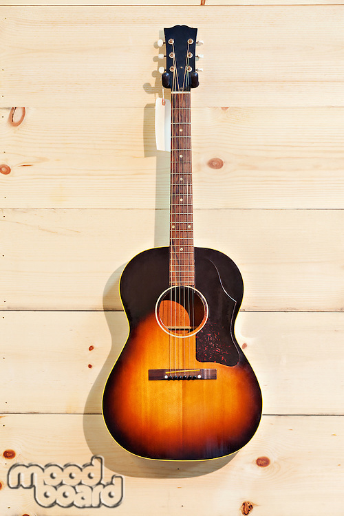 Acoustic guitar with label isolated on a wood grain wall