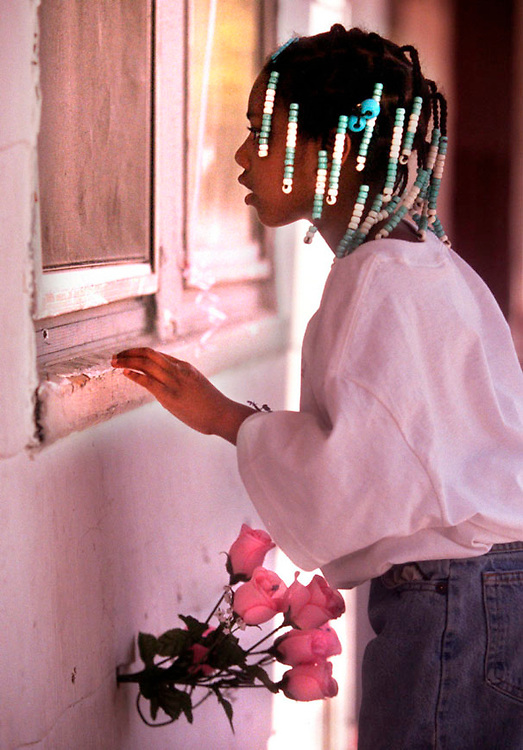 Alaziah Caddell, age 6, the cousin of murder victim Brianna Caddell peers into the first-floor bedroom window of the house on Cardoni Street, on Detroit's northeast side, where the 8-year-old was sleeping in her bed  April 10 when she was shot dead.  Relatives visited the house, that now sits vacant, while attending a birthday party in memory of Brianna nearby. Brianna's sister had placed a bouquet of pink silk roses in one of the bullet holes under the bedroom window.