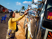 "14 FEBRUARY 2019 - SIHANOUKVILLE, CAMBODIA: A Cambodian woman who moved to Sihanoukville with her family sells an energy drink to a Cambodian truck driver at a construction site in Sihanoukville. She said they moved to Sihanoukville about a month ago hoping to find jobs in the Chinese financed boom in Sihanoukville. Her husband works as a construction laborer and she runs a small drink and snack stand. There are about 80 Chinese casinos and resort hotels open in Sihanoukville and dozens more under construction. The casinos are changing the city, once a sleepy port on Southeast Asia's ""backpacker trail"" into a booming city. The change is coming with a cost though. Many Cambodian residents of Sihanoukville  have lost their homes to make way for the casinos and the jobs are going to Chinese workers, brought in to build casinos and work in the casinos.      PHOTO BY JACK KURTZ"