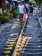 17 DECEMBER 2018 - BANGKOK, THAILAND: People walk next to railroad tracks near the Sukhumvit Road tourist district in central Bangkok. According to Credit Suisse Global Wealth Databook 2018, which surveyed 40 countries, Thailand has the highest rate of income inequality in the world. In 2016, Thailand was third, behind Russia and India. In 2016, the 1% richest Thais (about 500,000 people) owned 58.0% of the Thailand's wealth. In 2018, they controlled 66.9%. In Russia, those numbers went from 78% in 2016, down to 57.1% in 2018. The Thai government disagreed with the report and said the report didn't take government anti-poverty programs into account and that Thailand was held to an unfair standard because most of the other countries in the report are developed countries in the Organisation for Economic Co-operation and Development.      PHOTO BY JACK KURTZ