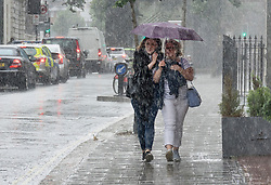 © Licensed to London News Pictures. 11/07/2017. London, UK. Two women shelter a baby under an umbrella as a sudden burst of heavy rain catches people out in central London. Photo credit: Peter Macdiarmid/LNP