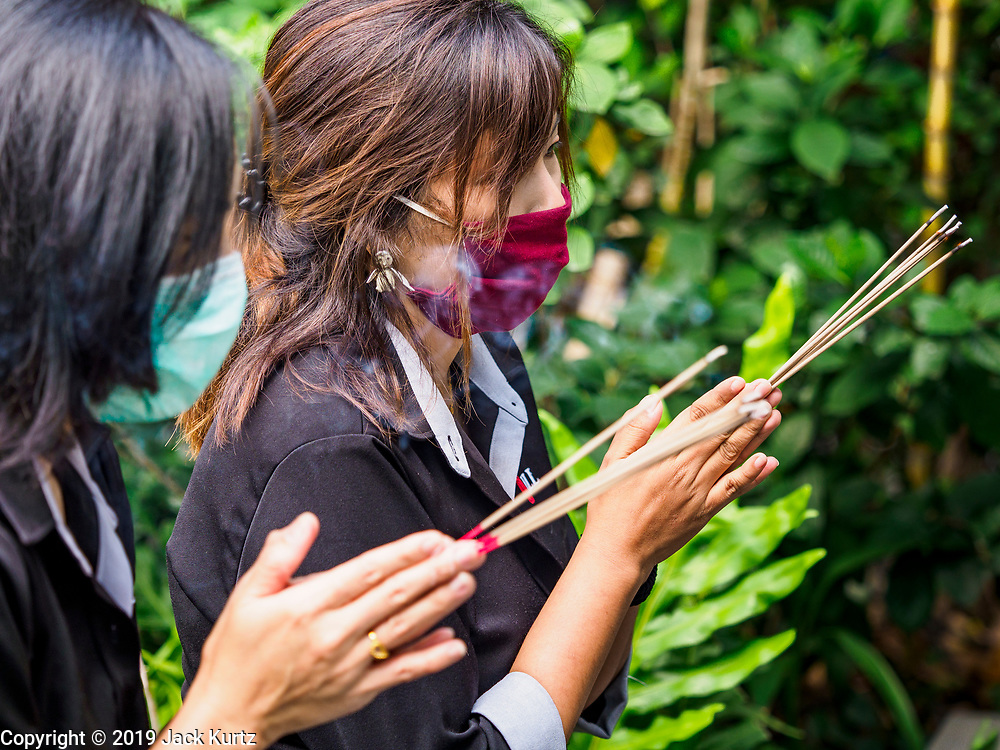 "31 JANUARY 2019 - BANGKOK, THAILAND:   Women wearing breathing masks prays with incense before going to work at an office tower in Bangkok. In an effort to control particulate pollution, the Thai government has asked people not to burn incense or ""gold paper"" for religious rituals. The Thai government has closed more than 400 schools for the rest of the week because of high levels of pollution in Bangkok. At one point Wednesday, Bangkok had the third highest level of air pollution in the world, only Delhi, India and Lahore, Pakistan were worst. The Thai government has suspended some government construction projects and ordered other projects to take dust abatement measures. Bangkok authorities have also sprayed water into the air in especially polluted intersections to control dust. Bangkok's AQI (Air Quality Index) Thursday morning was 180, which is considered unhealthy for all people.       PHOTO BY JACK KURTZ"