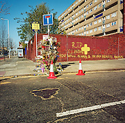 "This memorial has been placed where a young man called 'Clinton' died on the A1206 Manchester Road, London, England, UK. If we drove past this place where someone's life ended, the victim would just be an anonymous statistic but flowers are left to die too and touching poems and dedications are written by family and loved-ones. One reads: ""Your body is soft, not like street, Clinton."" From a project about makeshift shrines: Britons have long installed memorials in the landscape: Statues and monuments to war heroes, Princesses and the socially privileged. But nowadays we lay wreaths to those who die suddenly - ordinary folk killed as pedestrians, as drivers or by alcohol, all celebrated on our roadsides and in cities with simple, haunting roadside remembrances."