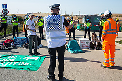 West Hyde, UK. 14th September, 2020. A Hertfordshire Police Incident Commander introduces a HS2 worker about to make a statement regarding the ownership of the property directly in front of him to environmental activists from HS2 Rebellion using lock-on arm tubes to block a gate to the South Portal site for the HS2 high-speed rail link. Anti-HS2 activists blocked two gates to the same works site for the controversial £106bn rail link, one remaining closed for over six hours and another for over twelve hours.