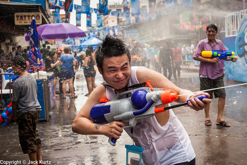 13 APRIL 2014 - BANGKOK, THAILAND: A tourist with a water gun on Khao San Road, Bangkok's backpacker district, during Songkran. Songkran is celebrated in Thailand as the traditional New Year's Day from 13 to 16 April. Songkran is in the hottest time of the year in Thailand, at the end of the dry season and provides an excuse for people to cool off in friendly water fights that take place throughout the country. Songkran has been a national holiday since 1940, when Thailand moved the first day of the year to January 1.    PHOTO BY JACK KURTZ