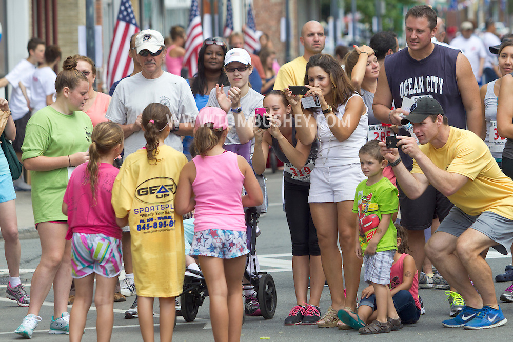 People take photographs of age-group winners at the Run 4 Downtown road race in Middletown, N.Y.