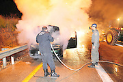 Israel, Northern District, firemen extinguish a burning vehicle