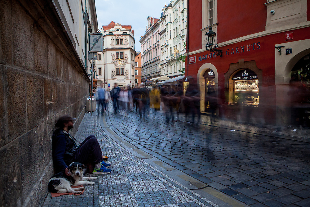 "A begging man beside the crowds of visitors moving through ""Karlova street"" which leads from the end of Charles Bridge towards Old-Town Square. The street belongs to the Royal Route - the name was given to a route, which for many centuries had been taken by the Czech kings in a procession to their coronation in the St. Vitus Cathedral at the Prague Castle"