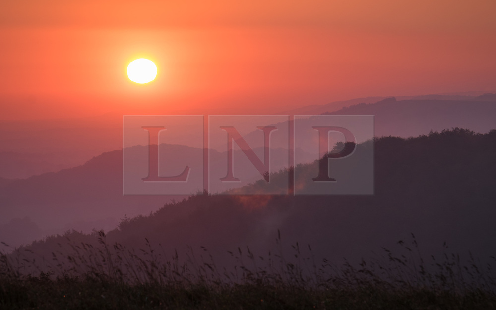 © Licensed to London News Pictures. 05/10/2016. Petersfield, Hampshire, UK.  Dawn breaks as the sun is seen rising over the South Downs National Park from Butser Hill in Hampshire this morning, 5th October 2016. Today will be another dry and sunny, but breezy, autumn day in the south of England. Photo credit: Rob Arnold/LNP