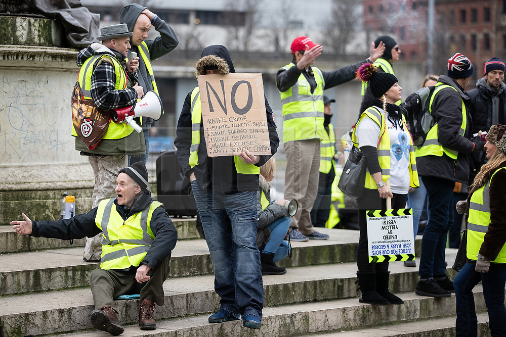 """© Licensed to London News Pictures . 05/01/2019. Manchester, UK. A man holds a placard against knife crime, """" mental illness jihad """" , Saudi funded shills , Brexit  betrayal and Jeremy Corbyn , in Piccadilly Gardens . A Yellow Vest demonstration takes place in St Peter's Square in central Manchester . The protest was organised via YouTube account """" Tommy Robinson News """" and was called in the wake of stabbings at Manchester Victoria Train Station on New Year's Eve . Protesters chanted in favour of Brexit , against police and press and carried pro-Trump and EDL clothing and placards . Photo credit : Joel Goodman/LNP"""