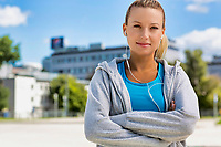 Portrait of young attractive woman standing with arms crossed while listening to music on her smartphone in park