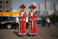 epa03002894 Waitresses dressed up in Qing dynasty costumes share a light moment while waiting to welcome customers outside a Chinese restaurant in Beijing, China, 14 November 2011. The Qing Dynasty was the last dynasty of China, they ruled from 1644 to 1912 and were Manchurians.  EPA/HOW HWEE YOUNG