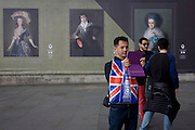 A tourist takes a photo with a modern device near Goya portraits, sponsored by Credit Suisse and advertised on a construction hoarding outside the National Portrait Gallery.