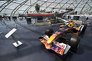 "Hangar-7; the spectacular home of the Flying Bulls (""Red Bull"" owner Didi Mateschitz' collection of classic airplanes) next to Salzburg W.A. Mozart airport. Original X-Wing Starfighter from ""Star Wars"" parked next to a Red Bull Formula One racing car themed ""Star Wars Episode III: Revenge of the Sith"", as driven by David Coulthard and Vitantonio Liuzzi in the 2005 Monaco Grand Prix."