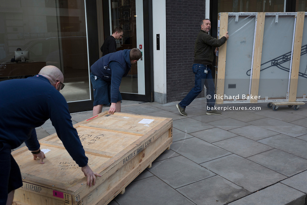 Deliverymen roll a flat crate containing artworks across the road and into a nearby art gallery on Hannover Square, on 5th March 2018, in London, England.