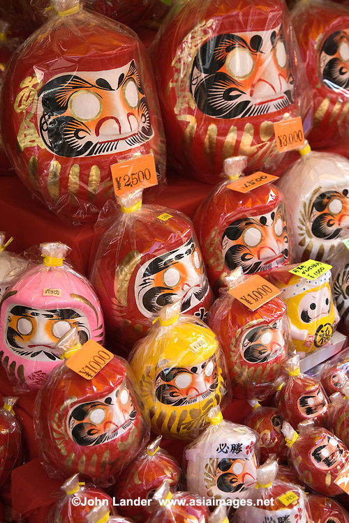 Daruma dolls are hollow and round Japanese wish dolls with no arms or legs, modeled after Bodhidharma, the founder and first patriarch of Zen Buddhism. The doll has a face with a mustache and beard, but its eyes only contain the color white. Using black ink, you fill in a single circular eye while thinking of a wish.  Should the wish come true the second eye is filled in.  It is traditional to fill in the right eye first; the left eye is left blank until the wish is fulfilled.