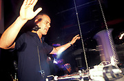 A white DJ raises his arms to the music at a club, U.K, 2000s.
